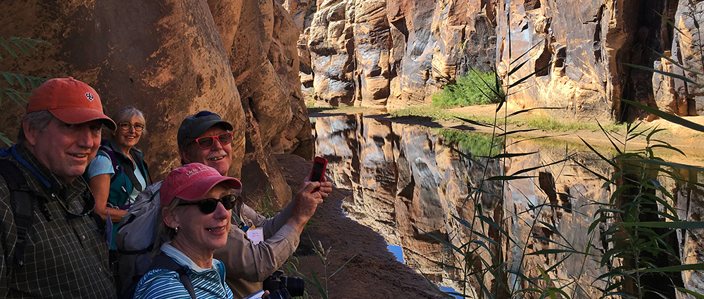4 adults at a canyon smiling for the camera and enjoying the river and red canyon walls.