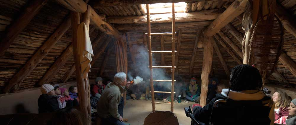 Latter up to opening in roof pit and an instructor teaching about the smoking ceremony  with a group of middle school students